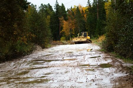 Crawler bulldozer rides on a dirt road in the autumn woods. Relocation of earthworks to another location