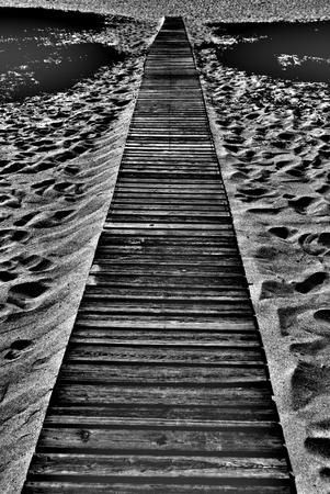 wooden walkway onto sandy beach black and white stock photo