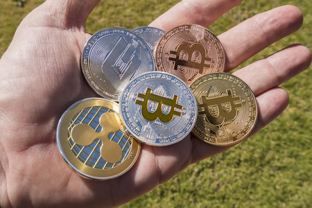 Cryptocurrency coins in a hand; Bitcoin, Ripple, Dash