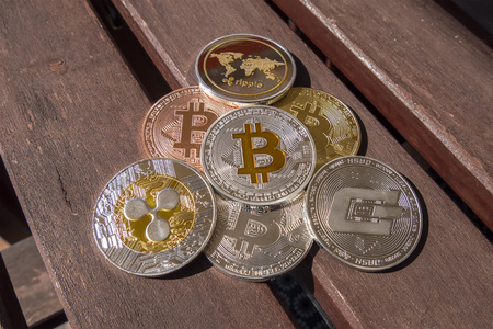 Cryptocurrency coins over a wood table; Bitcoin, Ripple, Dash