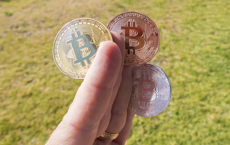 Cryptocurrency coins in a hand; Bitcoin