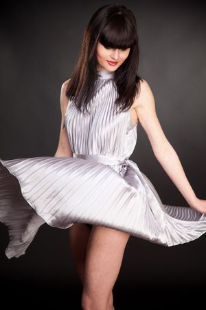 Playing girl in grey dress, isolated in studio shot