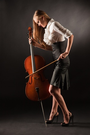 Elegant girl playing with passion on bass-viol, studio shot