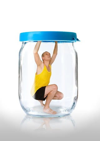 A man trapped in a glass jar  with the closed blue color lid