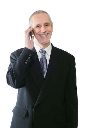 An amicable businessman smiling on mobile phone