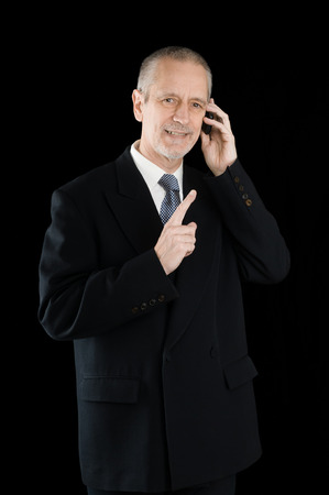 An agreeable businessman wearing a black suit smiling while speaking on mobile phone, on black background