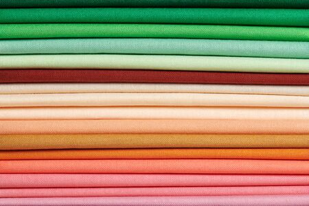 Photo pour Stack of bright self-colored cotton fabrics as a background image - image libre de droit