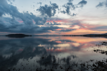Perfect and symmetric clouds and islands reflections on a lake, making abstract shapes with warm sunset colors