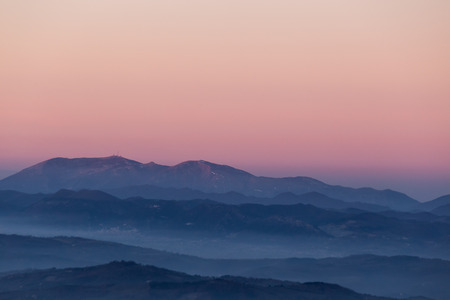 Photo for Beautifully colored sky at dusk, with mountains layers and mist between them - Royalty Free Image