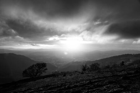 Photo for Moody sunset on Monte Cucco (Umbria, Italy), with tree in the foreground and sun filtering through clouds - Royalty Free Image
