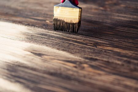 Photo pour Wooden boards are half covered with stain. A brush with a wooden handle and natural bristles on a background of painted wooden planks. The painting process, the layout. - image libre de droit