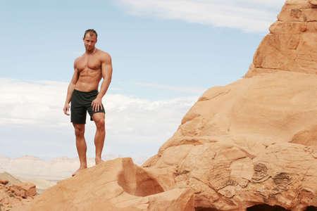 Handsome muscular man on red rocks