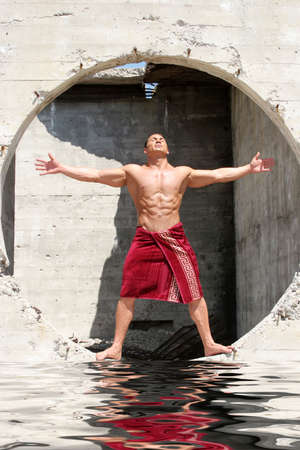 Muscular man posing in concrete structure