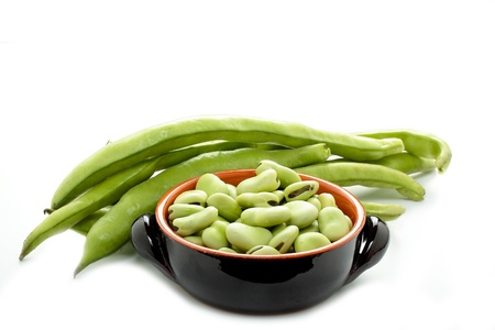 some raw broad beans on white background