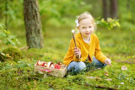 Photo pour Cute young girl having fun during forest hike on beautiful summer day. Child exploring nature. Active family leisure with kids. - image libre de droit