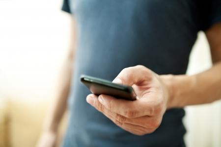 Photo pour Close up of a man using mobile smart phone  - image libre de droit