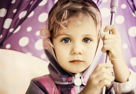 Little cute girl holding an umbrella, close up portraitの写真素材