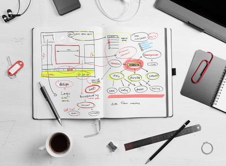 Developer workplace. Open notepad with hand drawn website project.