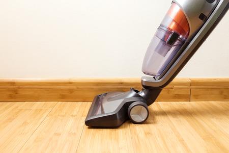 Cordless vertical vacuum cleaner cleaning parquet floor.
