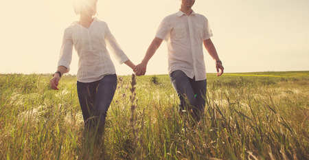 Happy couple holding hands walking through a meadow, tinted photo