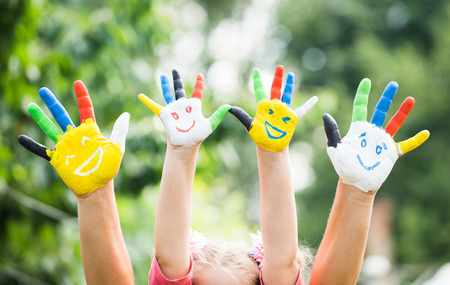 Photo pour Colored hands with smile painted in colorful paints against green summer background. Lifestyle concept - image libre de droit