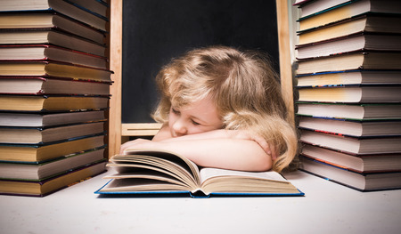 Young girl asleep on book at desk