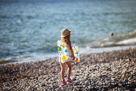 Adorable little girl with inflatable air mattress on beach