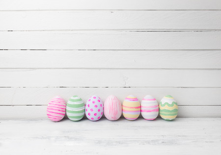 Photo for Easter eggs painted in pastel colors on white wooden background. Easter concept - Royalty Free Image