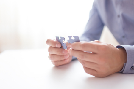 Photo pour Businessman hands connecting jigsaw puzzle. Business solutions, success and strategy, learning concept. Close up photo with small dof. - image libre de droit