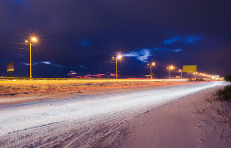 Photo for Winter snowy highway at night shined with lamps - Royalty Free Image