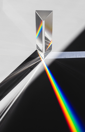 Foto de A prism dispersing sunlight splitting into a spectrum on a white background. - Imagen libre de derechos