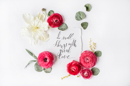 Phrase Do small things with great love written in calligraphy style on paper with pink, red roses, ranunculus,   white tulips and green leaves isolated on white background. Flat lay, top view