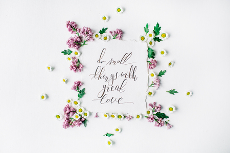 Phrase Do small things with great love written in calligraphy style on paper with wreath frame with lilac and chamomile isolated on white background. flat lay, overhead view, top view