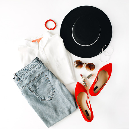 flat lay feminini clothes and accessories collage with blouse, jeans, sunglasses, bracelet, lipstick, red high heel shoes, earrings and hat on white background.