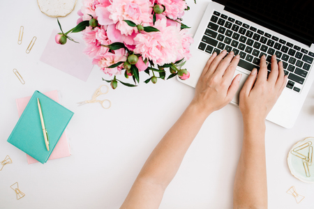 Flat lay home office desk. Workspace with woman hands, laptop, pink peony bouquet, golden accessories, mint diary. Top view