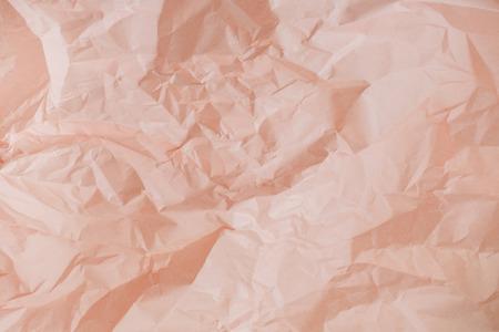Pastel peachy crumpled paper texture.