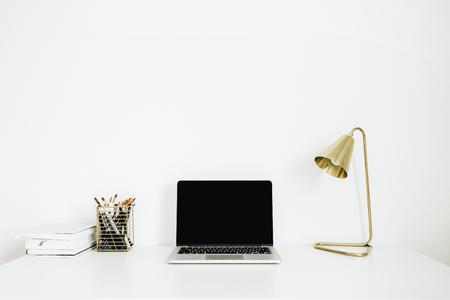 Home office desk workspace with laptop, golden lamp, stationery on white background. Minimalist modern interior design concept. Desktop mock up.