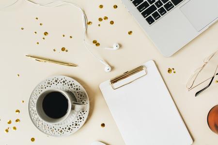 Minimalist home office desk workspace with clipboard, laptop, coffee, headphones on beige background. Flat lay, top view blog, social media, website hero header template.