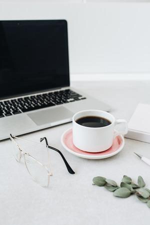 Minimalist home office desk workspace. Laptop, coffee, glasses, notebook, eucalyptus.