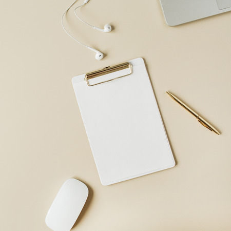 Minimalist home office desk workspace with clipboard, laptop, headphones on beige background. Flat lay, top view modern lifestyle copy space mock up.