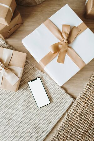 Christmas / New Year gift boxes with bows. Smart phone with blank copy space mock up screen. Traditional winter holidays gifts packaging creative concept. Flat lay, top view.