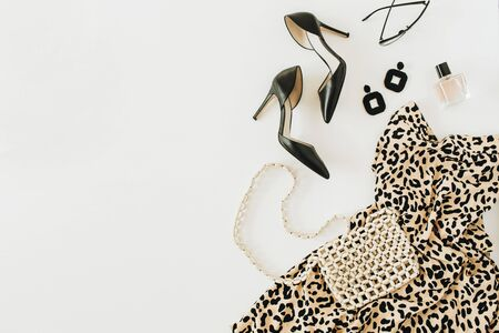 Photo pour Modern fashion collage with female clothes and accessories. Leopard print dress, high-heel shoes, earrings, glasses, purse, perfume on white background. Flat lay, top view. - image libre de droit