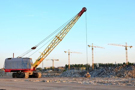 Photo for Large crawler crane or dragline excavator with a heavy metal wrecking ball on a steel cable. Wrecking balls at construction sites. Dismantling and demolition of buildings and structures - Image - Royalty Free Image