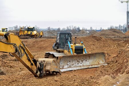 Photo pour Excavator and a bulldozer work at a construction site. Land clearing, grading, pool excavation, utility trenching and foundation digging.  Laying of underground storm sewer pipes. - image libre de droit
