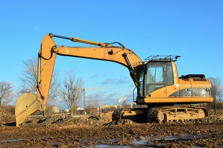 Foto de Tracked excavator working at a construction site during laying or replacement of underground storm sewer pipes. Installation of water main, sanitary sewer, storm drain systemsduring - Image - Imagen libre de derechos