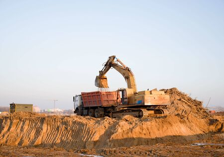 Foto de Excavator load the sand to the dump truck on construction site. Backhoe digs the ground for the foundation and construction of a new building. - Imagen libre de derechos