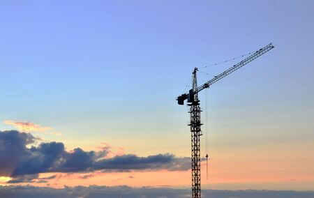 Photo for Jib construction tower crane and new residential buildings at a construction site on the sunset and blue sky background - Image - Royalty Free Image