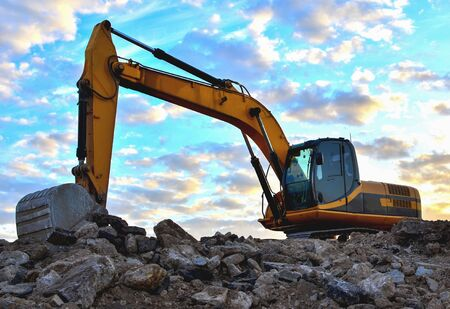 Photo pour Excavator loads of stone and rubble for processing into cement or concrete for construction work and reuse. Backhoe at quarry. Develop the glavel or sand and blocks of rock. Soft focus, tinted - image libre de droit