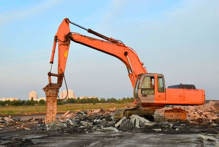 Photo for Crawler excavator with hydraulic hammer for the destruction of concrete and hard rock at the construction site - Royalty Free Image
