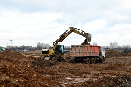 Photo for 08.11.2019 Minsk, Belarus: Wheeled excavator CATERPILLAR load the sand to the heavy dump truck MAZ on construction site. Dig the ground for the foundation and construction of a new building. - Royalty Free Image